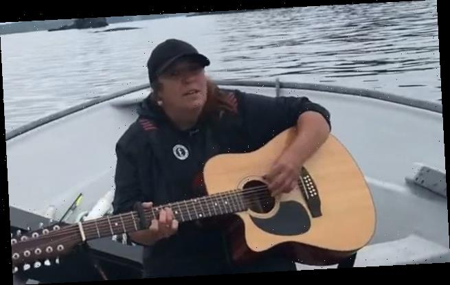 Women are amazed as whales swim to their boat when they play guitar