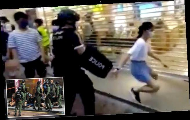 Girl is wrestled to the ground by Hong Kong riot police at protests