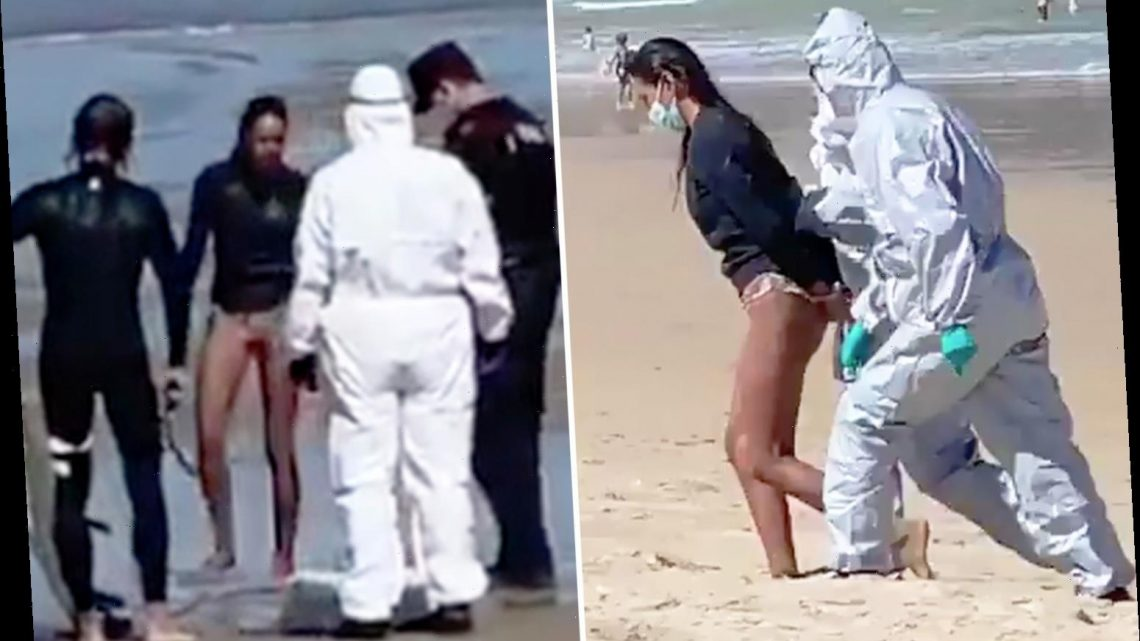 Female surfer dragged off Spanish beach in cuffs by hazmat-clad cops for 'riding waves while infected with coronavirus'