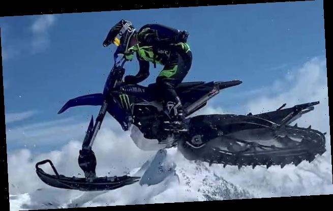 Adrenaline junkie rides his snowbike off the edge of a cliff